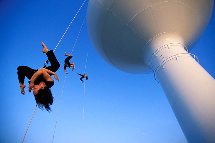 An aerial dance ballet perform suspended from a water tower.